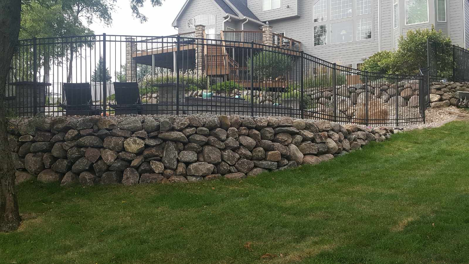 executive black iron fence with rock